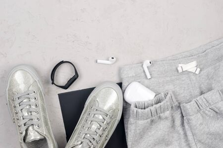 Monochrome women's background. Sports grey clothing, fitness bracelet and headphones, sneakers, socks and knitted pants on grey and black background. Flat lay female casual style look. Top view. Фото со стока