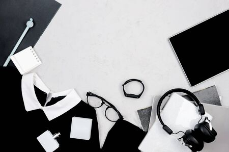 Monochrome background with women's outfit set in office style, accessories, tablet and Office or school supplies on grey. Concept online work or study. Flat Lay female casual style look. Top view. Archivio Fotografico
