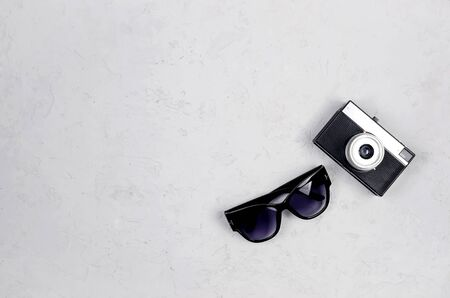 Monochrome Summer background with women's sun glasses and retro camera on grey concrete, Top view, flatlay, mock up. Travel concept, template for text. Zdjęcie Seryjne