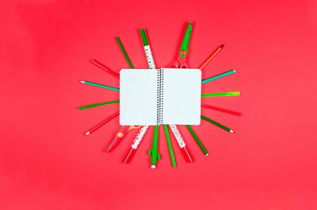 Notebook, colored school supplies on red background. Education concept. View from above with copy space. Mockup, flat lay