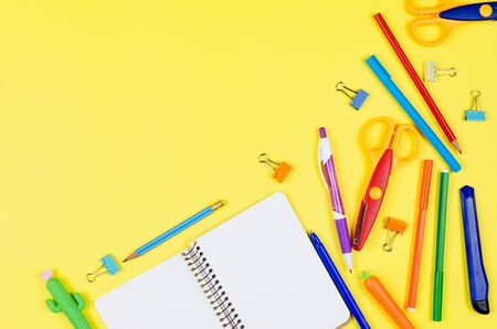 Colored different school supplies on soft yellow paper background. Notebook, pens, pencils and other tools. Back to school background. Flat lay, top view, copy space. Banner for site.