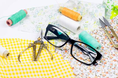 Set of colorful yellow and green fabrics, scissors, buttons, spools of thread and glasses on white. Concept for tailoring, patchwork and handwork. Needlework and Sewing.
