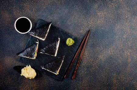 Tasty sushi sandwiches with salmon on black stone plate with soy sauce, ginger, wasabi and chopsticks on dark table. Sushi menu. Japanese Asian food. Delivery service. Trend hybrid food.