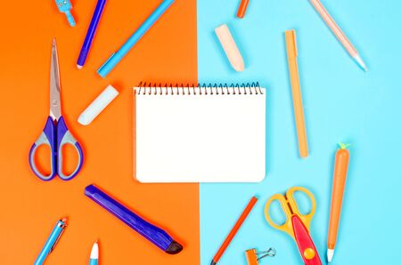 Notebook, blue and orange school supplies on blue background. Education concept. View from above with copy space. Mockup, flat lay