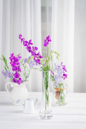 purple wildflowers in a glass vase in a white interior