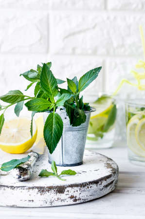 mojito cocktail in glass, lemons and mint leaves in basket on white wooden table, cocktail summer drinks concept Stock fotó