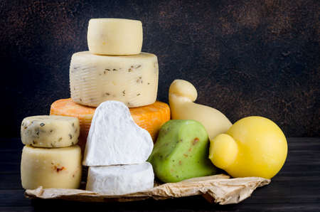 cheese heads of different kinds stacked on table