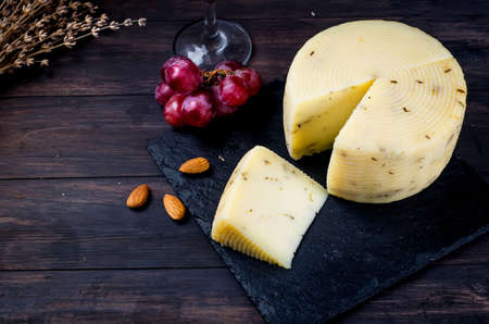 homemade cheese head with lavander on old dark wooden board and glass of wine on table. Fresh dairy product, healthy organic food. Delicious appetizer.
