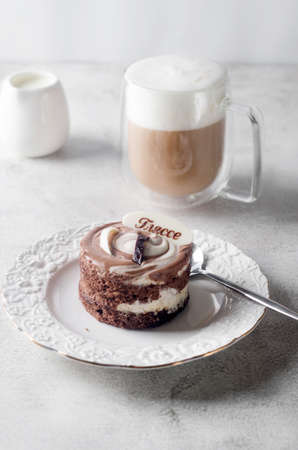 Chocolate mini cake in elegant white plate and cappuccino with froth in glass cup on light gray background, top view. Delicious dessert. Breakfast table place setting. 免版税图像