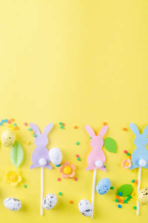 Easter greeting card with place for text. Blank note, Easter eggs, decorations and sweets on yellow background. Mock up for design. template for congratulations 免版税图像
