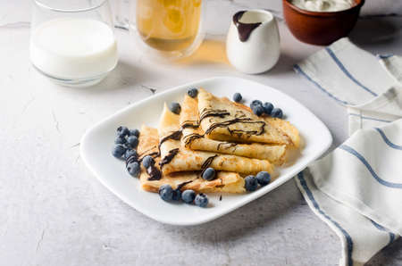 Homemade crepes, tasty thin pancakes with chocolate and berries on a white plate for breakfast with cup of tea. Traditional Russian cuisine.