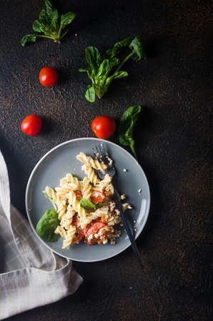 Italian dish of pasta mixing with Feta cheese baked and tomatoes on a dark background. Fetapasta. Trending viral recipe, Flat lay, copy space