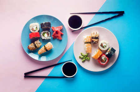 Tasty sushi rolls set on blue plate with sauces, chopsticks, ginger and wasabi on colored background. Sushi menu. Delivery service Japanese food. Assorted sushi, rolls, gunkan, nigiri.