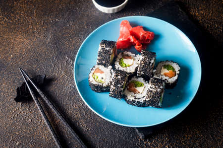 Tasty sushi rolls set in black sesame on blue plate with black chopsticks, ginger and wasabi on dark background. Sushi menu. Delivery service Japanese food.