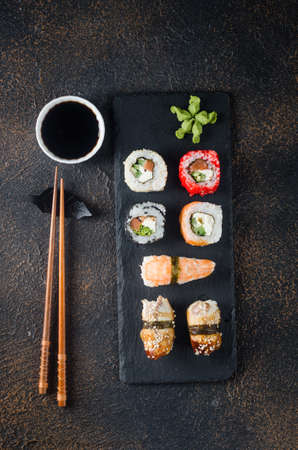 Tasty sushi rolls set on black plate with sauces, chopsticks, ginger and wasabi on dark table. Sushi menu. Delivery service Japanese food. Assorted sushi, rolls, gunkans, nigiri.
