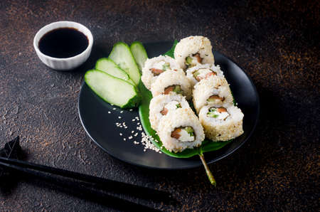 Tasty Philadelphia roll sushi with salmon and cream cheese in sesame on black plate with soy sauce, ginger, wasabi and chopsticks on dark table. Sushi menu. Delivery service Japanese Asian food. 免版税图像