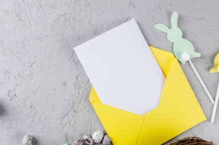 Empty Easter greeting card with place for text. Envelope with blank note, Easter eggs, decorations and tulips on gray concrete background. Mock up for design. template for congratulations