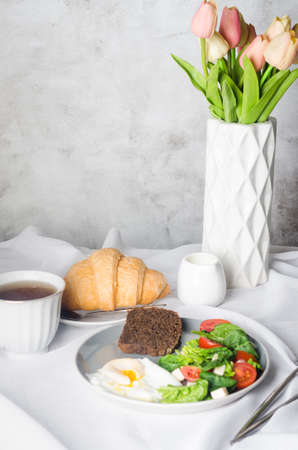 Morning spring table setting decoration. Salad in plate, egg, cup of coffee and croissant, fresh tulips in vase on clean white tablecloth background. Breakfast table place setting in white color.