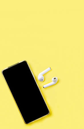 Smartphone with Blank Screen with Earphones on yellow paper Background Top View. Concept listen to music, cast, audio from smartphone.