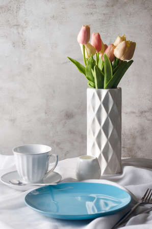 Morning spring table setting decoration. Empty ceramic plate, cup, fresh tulips in vase on clean white tablecloth background. Dinner or breakfast concept,