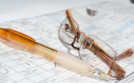 Image of the pen, glasses placed on the crossword (scanword) photo