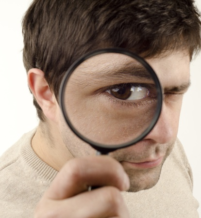 magnifying glass man: Image of young man looking through a magnifying glass Stock Photo