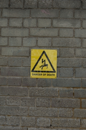 Image of danger sign on brick wall photo