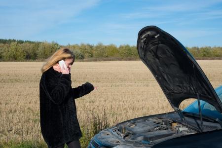 broken car: image of Beautiful blond girl calling cellphone near her broken car