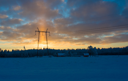 Image of an unusual view of the high voltage tower on a snowy meadow photo
