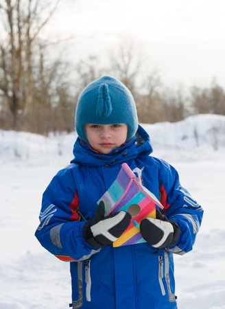 Cute boy with bird feeder. Winter time photo