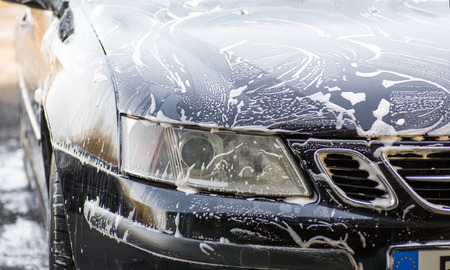 Image of part of car covered with soap foam photo