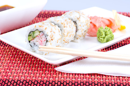 Image of Sushi rolls with sticks and plate photo