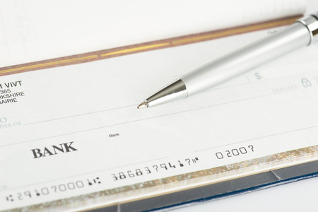 commercial activity: Image of Close up photo of a pen and blank dollar check. Shallow focus