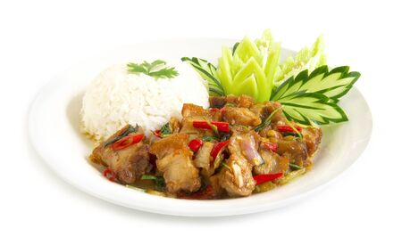 Thai food stir-fried crispy pork spicy and Thai basil served with rice and cucumber,green peppers carved white plate side view isolated on white background