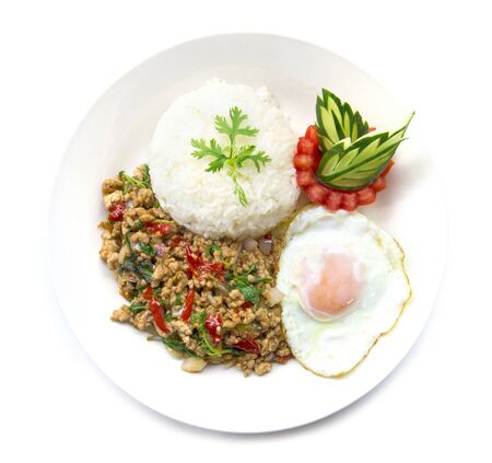 Thai food stir-fried pork spicy and basil served with rice and fried egg and tomato cucumber carved white plate top view isolated on white background Imagens