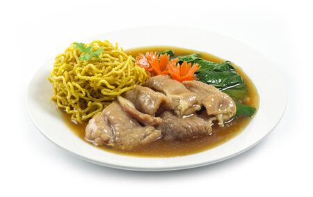 Crispy Egg Noodles with pork ,kale Chinese vegetables in gravy soy sauce soup Chinese style decorate with carved carrots popular food in street food of Thailand side view Banco de Imagens