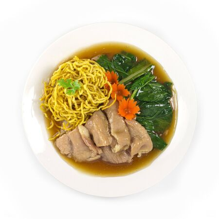 Crispy Egg Noodles with pork ,kale Chinese vegetables in gravy soy sauce soup Chinese style decorate with carved carrots popular food in street food of Thailand top view