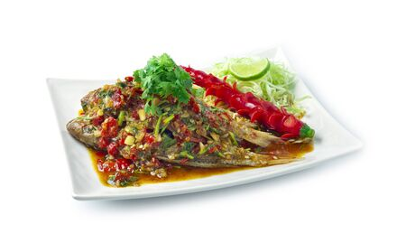 Fried Fish with sweet chili sauce Thai spicy food style decorate with vegetables chili side view