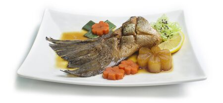 Salmon Tail in soy sauce soup Japanese food fusion style decorate vegetables carved and carrot,lemon side view