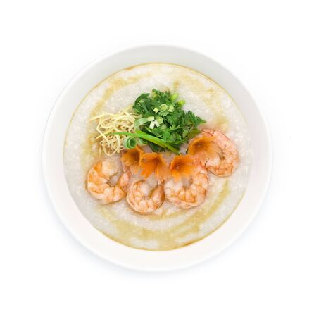 Congee Shrimps ,Rice Porridge served slice ginger and cutlet Celery,coriander thai herb. Asian Food breakfast decorate with carved carrots and spring onion top view