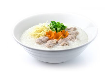 Congee Pork Rice Porridge served slice ginger and cutlet Celery. Asian Food breakfast decorate with carved carrots side view Stock Photo