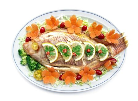 Steamed fish (Tilapia fish) on top lemon slice with carved carrots tomato vegetables style healthy food, diet food top view isolated on white background