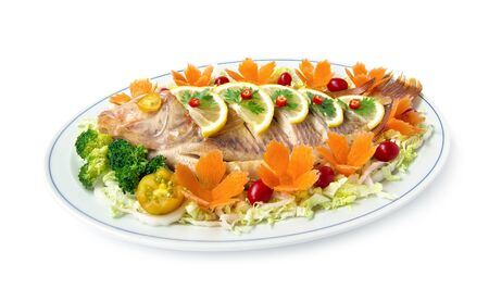 Steamed fish (Tilapia fish) on top lemon slice with carved carrots tomato vegetables style healthy food, diet food side view isolated on white background