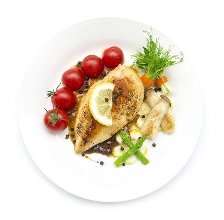 Grill Hähnchen oder Hähnchensteak mit schwarzer Paprika-Sauce garniert mit schwarzen Paprikaschoten, Spargel, Austernpilz, Tomate und Zitrone, geschnitzte Draufsicht einzeln auf weißem Hintergrund