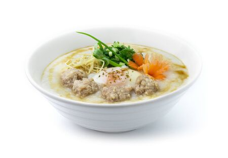 Congee Pork ,Rice Porridge with Boiled Egg served slice ginger and cutlet Celery,coriander thai herb. Asian Food breakfast decorate with carved carrots and spring onion side view