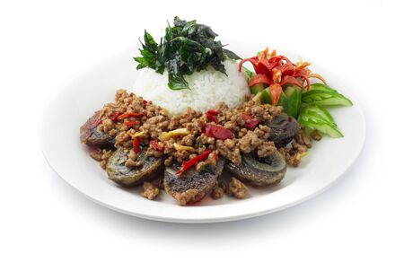 Thai Food Stir-fried Preserves Eggs,Century Egg with Pork hot Spicy with Thai Basil served rice on top Crispy Thai Basil decorate carved chili and cucumber side view