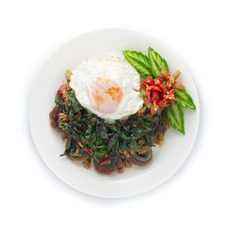 Thai Food Stir-fried Preserves Eggs,Century Egg with Pork hot Spicy with Thai Basil served rice ontop fried Egg and Crispy Thai Basil decorate carved chili and cucumber top view