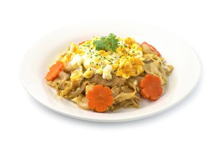 Thai food Stir fried Noodles with pork,egg and Chinese kale in black soy sauce (Pad See Ew Moo) Thai Street food fusion style decorate carved carrot side view Stock Photo