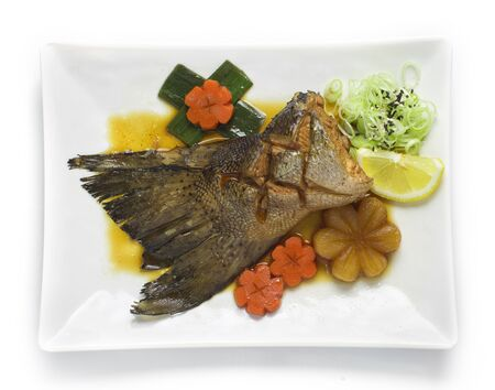 Salmon Tail in soy sauce soup Japanese food fusion style decorate vegetables carved and carrot,lemon top view Foto de archivo