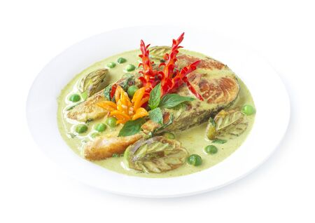 Green Curry with Salmon in coconut milk sauce Spicy Thai food fusion style decorate vegetables carved chili and Thai basil side view